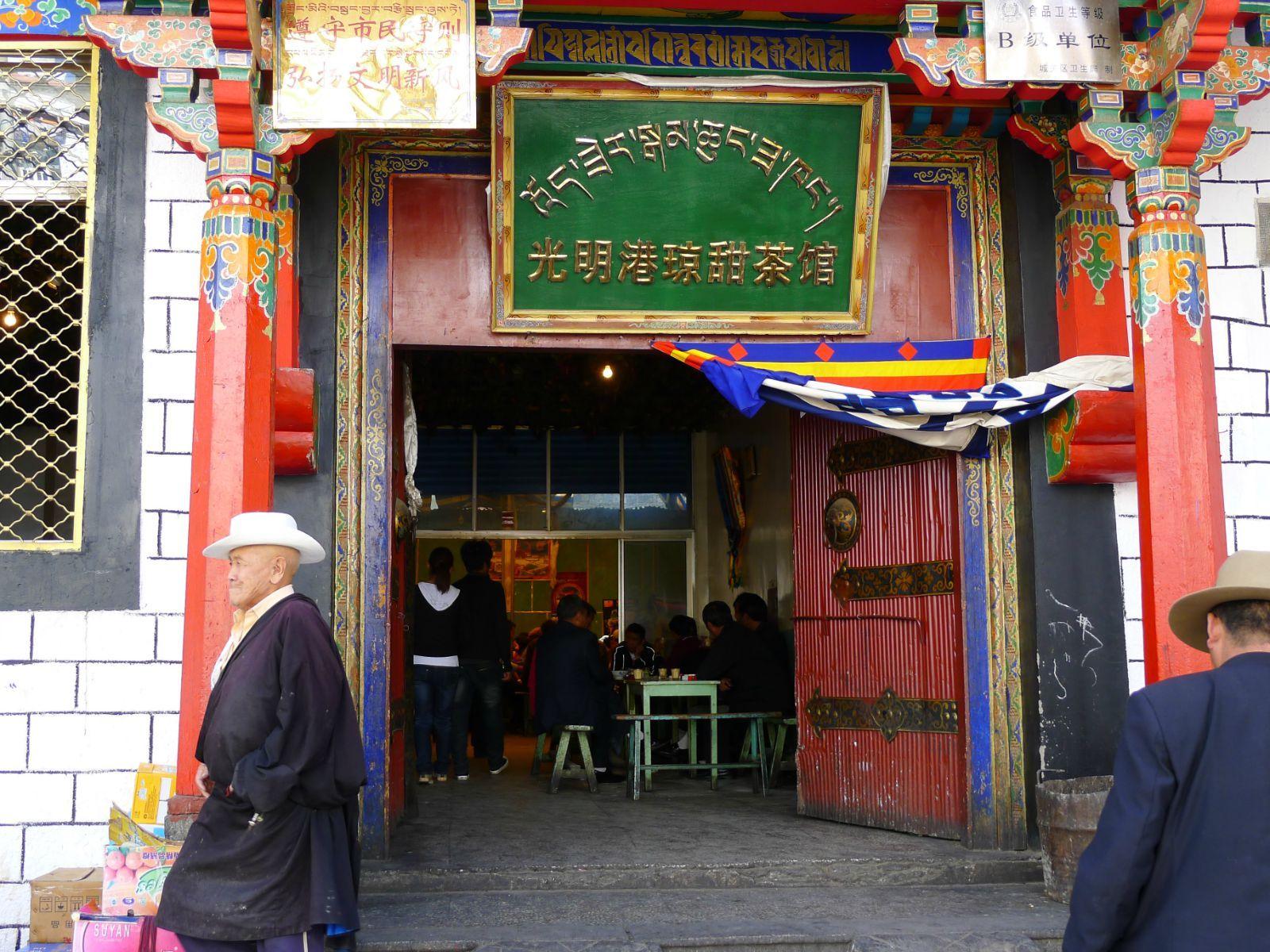 光明港琼甜茶馆门口就是到大昭寺的主要通道丹杰林路,商业繁荣,加上茶馆的价格地道,虽然内部环境很一般,就是一个简单的集体食堂一般,但这个茶馆名气、人流量在当地都是最大的。甜茶馆门不大,很有藏式风格,进了大门,里面大厅很宽敞,有好几排长条矮桌,很有藏式风格,其实这大厅就是院子上面打了个顶棚而已,茶馆汇集着各种身份的人,简直是人满为患,藏民在这里就像成都人泡茶馆一样,一呆就是半天。这里是西藏最市井的地方,当然也是我们这些游客体验民风的好地方,不时的进来一队队游客,据说偶尔也会碰到很多老外在这里喝茶。不管你能否听
