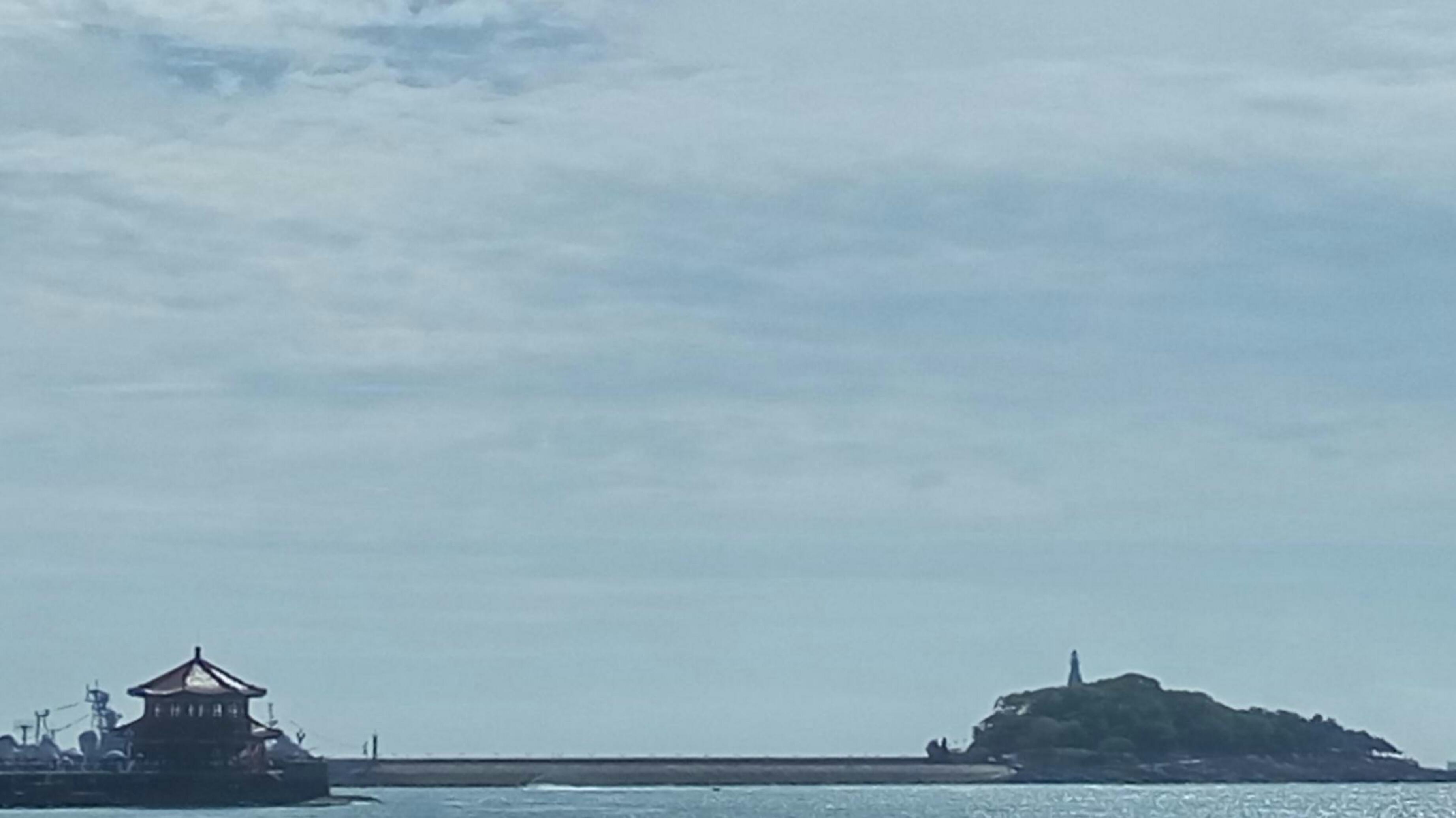 游人漫步于栈桥海滨,可见栈桥似长虹卧波,回澜阁熠熠生辉.所谓长虹远引、飞阁回澜所指即此.远处,树影婆娑、绿荫哝哝,一座白灯塔亭亭玉立.湾东侧和北侧,红瓦绿树交相辉映,各式建筑参差错落的分布在海岬坡地之上.湾西侧的现代化高层建筑紧靠海岸拔地而起,壮丽恢宏.沿岸的防波堤由花岗岩垒砌,高出水面10余米.