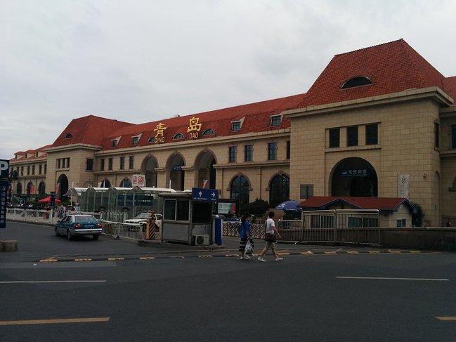 青岛火车站位于青岛市中心,距离海边仅两百多米。这是一组建于1899年的德国文艺复兴风格建筑,它拥有醒目的红瓦黄墙,以及一座尖顶的钟楼,外形很漂亮也很文艺。青岛火车站至今仍在使用,是青岛的地标建筑之一。青岛火车站主要由钟楼和候车大厅两大部分组成。它是由德国人魏尔勒和格德尔茨设计的,这坐火车站再现了设计师家乡的建筑风格,尤其是35米高的车站钟楼,更是沿用了德国乡间教堂样式。一百多年间,车站钟楼上行走的时钟一刻不停地记录了那些行色匆匆的旅客们。