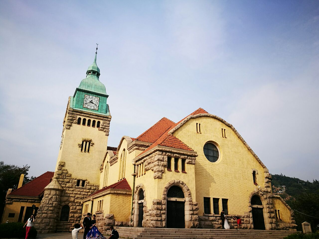 位于龙山路和江苏路附近的这座基督教堂,原名福音堂,是青岛著名的宗教建筑。1910年10月落成,距今已有100多年的历史了。这是座典型德国建筑风格的教堂,基督教堂整体建筑均由石头堆砌而成,分为礼堂和钟楼两部分,站在远处观看,黄色和绿色的搭配更有一种童话的感觉!绿色铜片、红色筒瓦、蘑菇石、三口钟均为1909年原装设备,机械报时钟历经风雨历经岁月,依旧运行正常,钟表时间至今仍然分秒不差!去参观时有幸赶上了一场完整的教堂婚礼,新郎和新娘在神的见证下,在众人的祝福中,郑重宣誓、生老病死、不离不弃,一起携手走向红毯的