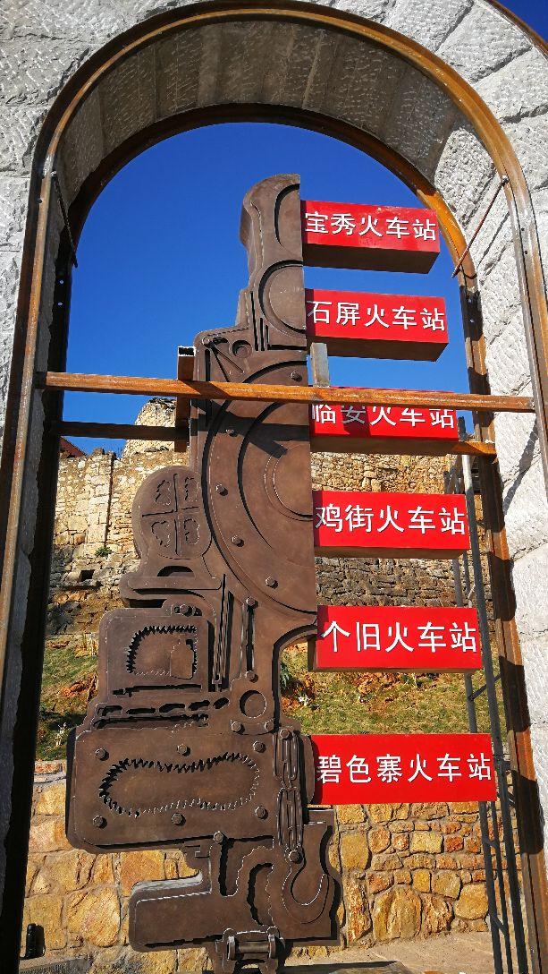 碧色寨位于红河哈尼彝族自治洲蒙自县的草坝镇,是中国近代史上最早的火车站之一。这里渗透了众多中国劳工的血汗,也见证了一段段历史。车站至今仍保留着法国式铁路用房,挂在车站墙上饱经风霜的时钟,英文Paris(巴黎)字样依然清晰可见,让人想起当年的繁华。 碧色寨是滇越铁路上百年老站。这座边地火车站是火车迷们的必游之地,也是摄影爱好者的心头好。除了铁路边上那些黄色的老房子,铁路两边山坡上还有许多古旧的建筑,包括以前法国人的养牛房、站长室、职工食堂、酒吧。当年此地不仅车水马龙,更是洋人汇聚之地。现在这里有一幅木制地图