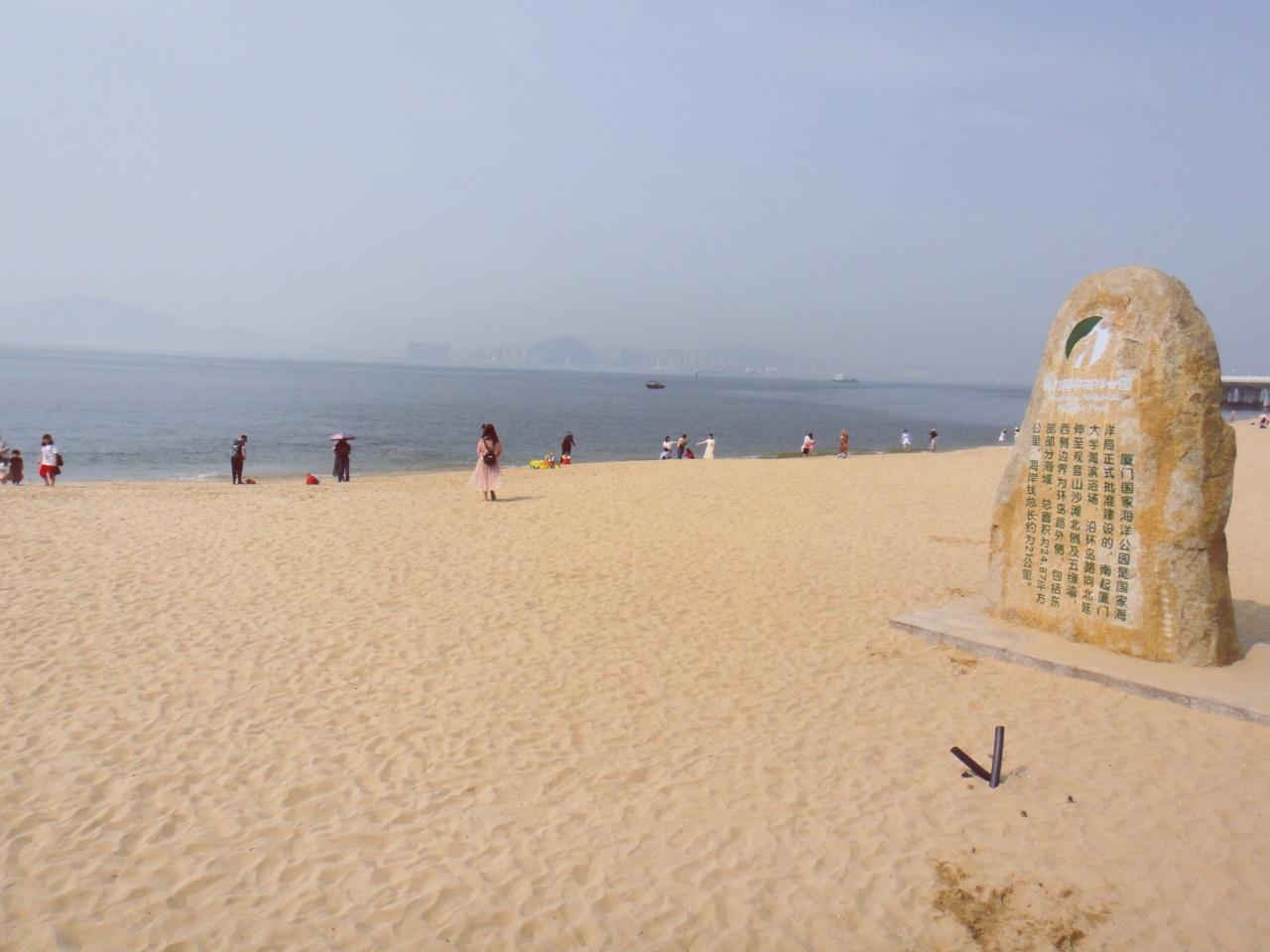 """随后我们就沿着环岛路逛,由于天空又再一次淅淅沥沥的下起了雨,我们无法在沙滩漫步,近距离的感受属于厦门的海滩。但是这里是一个环境非常优美的消遣时光之处,音乐广场集艺术性与纪念性、知识性为一体,这里是曾经""""跑男""""厦门站的拍摄地。一国两制沙滩纪念香港澳门回归统一政策,沙滩地址正向着海域对面的金门县岛屿,可以一海之隔看台湾。 这里还是看日出日落的好去处,顺便抓取之前拍摄的照片让大家感受."""