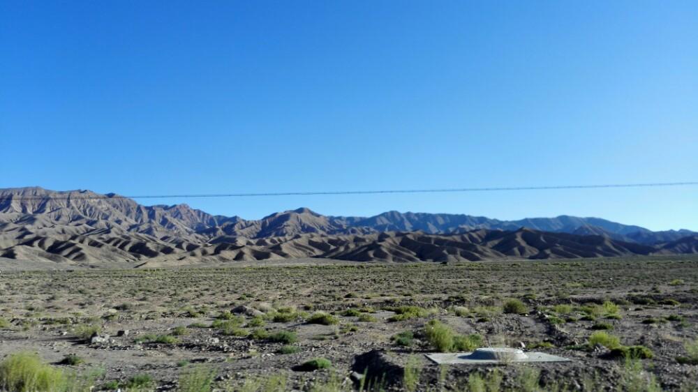柴達木盆地是沒有門票的,但也沒什麼人氣,可能是太偏遠了,沒有大巴也沒有公交,我報團去的,路上的景色還不錯,茫茫戈壁,偶爾會見到散落的鹽湖,這種開闊的景象在車上看一點不覺得乏味。距離是蠻遠的,幸好交通相當通暢,一路上迎面的、同向的,也沒遇上幾輛車。不知是當初是怎樣修成的這條公路,應該耗費了不少人力物力財力吧。車里有空調,感覺還比較舒服,一下車直接熱蒙了,適應了好一會兒。沙丘,戈壁灘,一眼望去,跟大海一樣,都是無邊無際的感覺,但海是柔美的,浪漫的,沙漠有的卻是壯美,蒼涼。我們那個散客團里很多攝影愛好者,放下腳