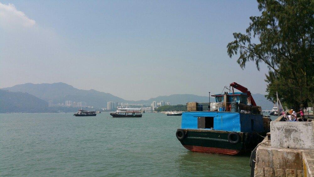 在天星码头坐渡轮到中环七号码头,到坪洲的船刚好在旁边的六号码头,往坪洲的船有快船和慢船,慢船的航程约45分钟,港币15.3元,大约每45分钟一班船。坪洲岛与香港大都市的节奏截然不同,悠闲自在,坪洲码头附近停靠有不少快艇、有政府的大楼、街市、茶餐厅、超市等,人们在榕树下歇息、喝茶。岛内的小餐厅有卖快餐的烧腊店、茶餐厅,据说有几十年历史的冰室正在重新装修,明年初才重新开业,制作著名的坪洲虾饼的档口也没有营业。岛上的商铺一般都是居民的私人住宅改建的,无需交铺租,因而没有压力,商铺开门的时间表就是老板心情的晴雨表