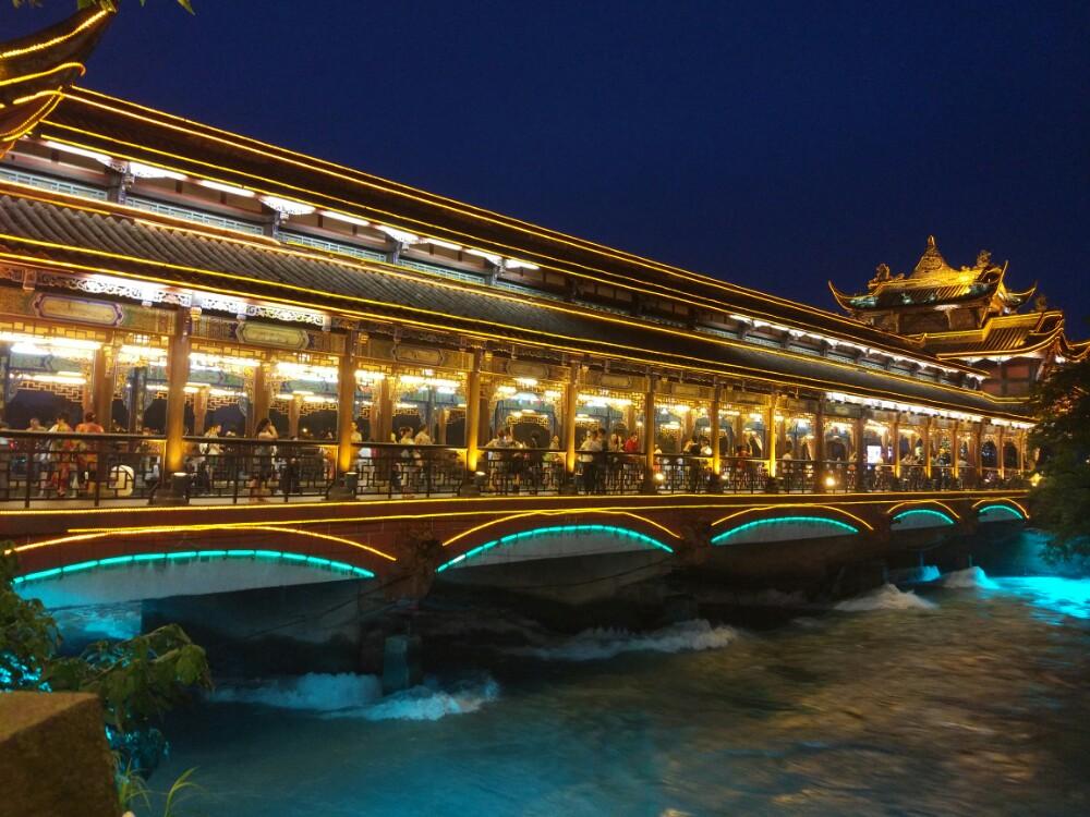 南桥是一座仿古廊桥,廊桥的天棚有彩画天花及卷棚仿古天棚,所有的木雕进行描金填彩。廊桥边上有一条热闹的美食街,能够吃到各种当地的美食。夜晚的廊桥特别美丽,吹江风,吃小吃,欣赏夜景,非常惬意。 南桥位于都江堰宝瓶口下侧的岷江内江上,原名为普济桥,曾多次损毁,1959年重建,更名为南桥, 1979年再次维修。桥头阔面三间,牌楼式三重檐桥门厅型,屋面为筒瓦屋面,泥塑各类脊、瓜角、走兽、人物等,桥头有木雕、吊爪、龙头、过江花板、木雕挂落等。