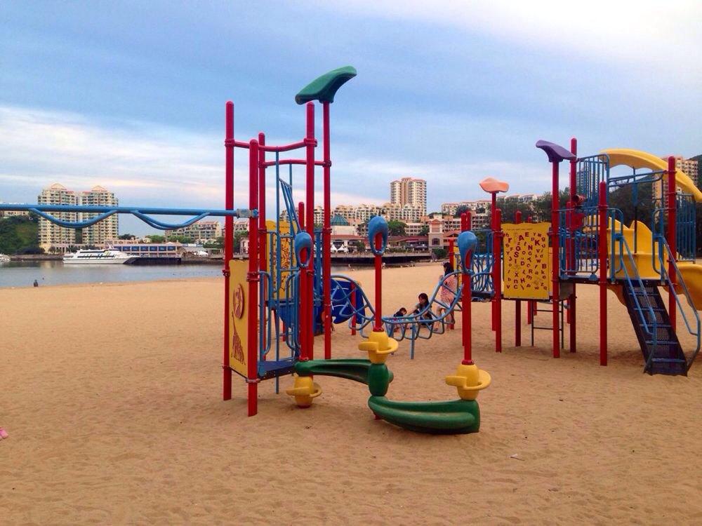 沙滩上有儿童游乐设施,女儿荡了很久的秋千.