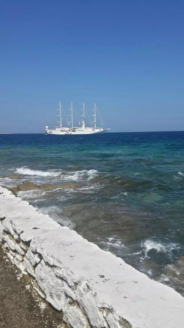 米克诺斯岛和圣托里尼岛是美国国家地理杂志旅行者推荐的人一生要去的的50个地方( 50 places of lifetime)中十大人间天堂之一-希腊群岛中最为著名的岛屿之一,又被称为最接近天堂的岛屿。不过,游了2天也没有搞明白为什么叫最接近天堂?米克诺斯以她阳光充足的沙滩、传统而风格独特的建筑(白如羽毛的墙壁)、迷人热烈的夜生活,还有幽静、迷宫般的小巷,成为大受欢迎的旅游胜地。小岛著名的景点包括:霍拉小镇、小威尼斯、风车阵(但不如阿姆