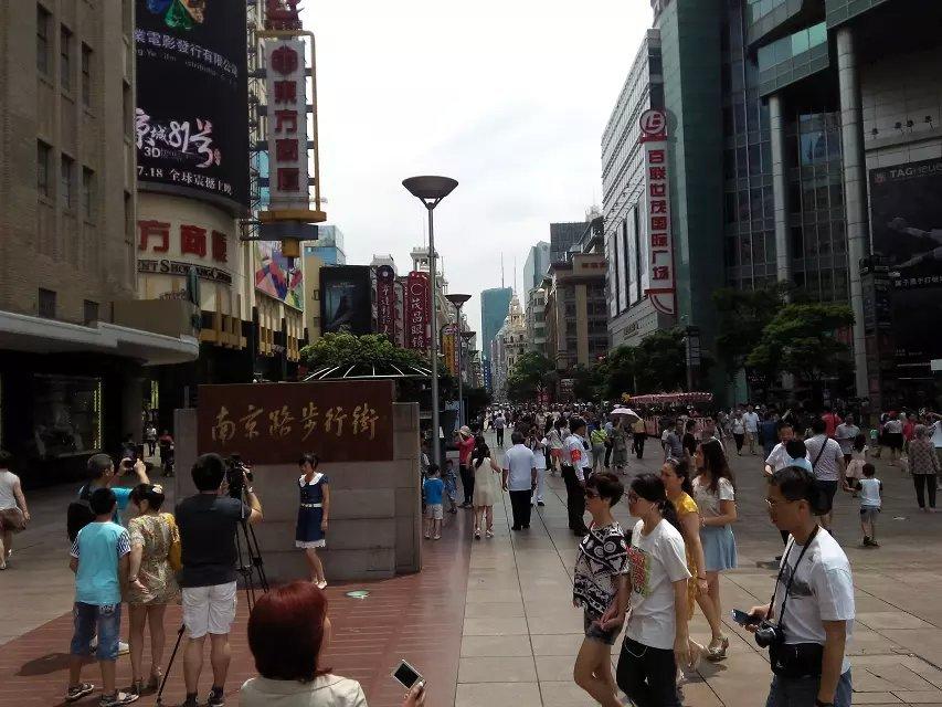 南京路步行街是特指南京東路這一段,從西藏北路起到河南北路止。上海的道路東西以城市命名,南北以省份命名。90年代初的時候,南京路還是一條跑車的路,來往的公交車、出租車、行人擁堵得很,而且很容易出交通事故。那時候,在南京路步行街西藏北路這一頭有一座圓形的天橋,走上天橋,走可以進入到十字路口四個方向的商廈。小時候最常去的是第一人民百貨商店,我們稱之為市百一店,市百一店對面是精品商廈,後來拆除了。再往里是第一人民食品商店,以前過年過節的時候這里就人山人海採購食物,現在還是如此,在老上海人的心里這個食品店就是賣最好