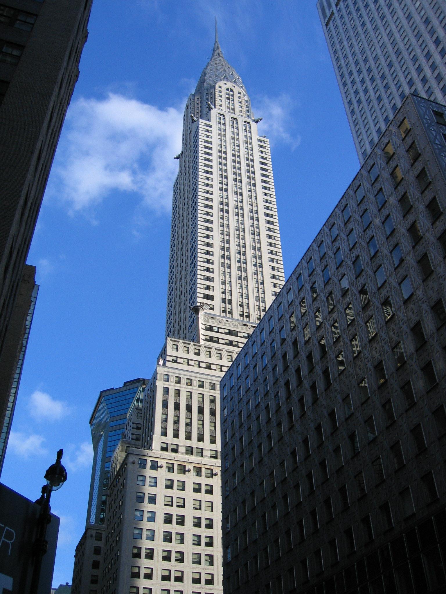 克萊斯勒大樓----位於曼哈顿中城42街與列星頓大道交口在紐約市樓高爭奪戰中克萊斯勒以風格獨具取勝全球首座以不鏽鋼建材運用在外觀的建築大樓頂端酷似太陽光束的設計是1930年一款克萊斯勒汽車的冷卻器蓋子以汽車輪胎為構想五排不銹鋼的拱形往上逐漸縮小每排拱形鑲嵌三角窗呈鋸齒狀排列高聳的尖塔成為這棟不
