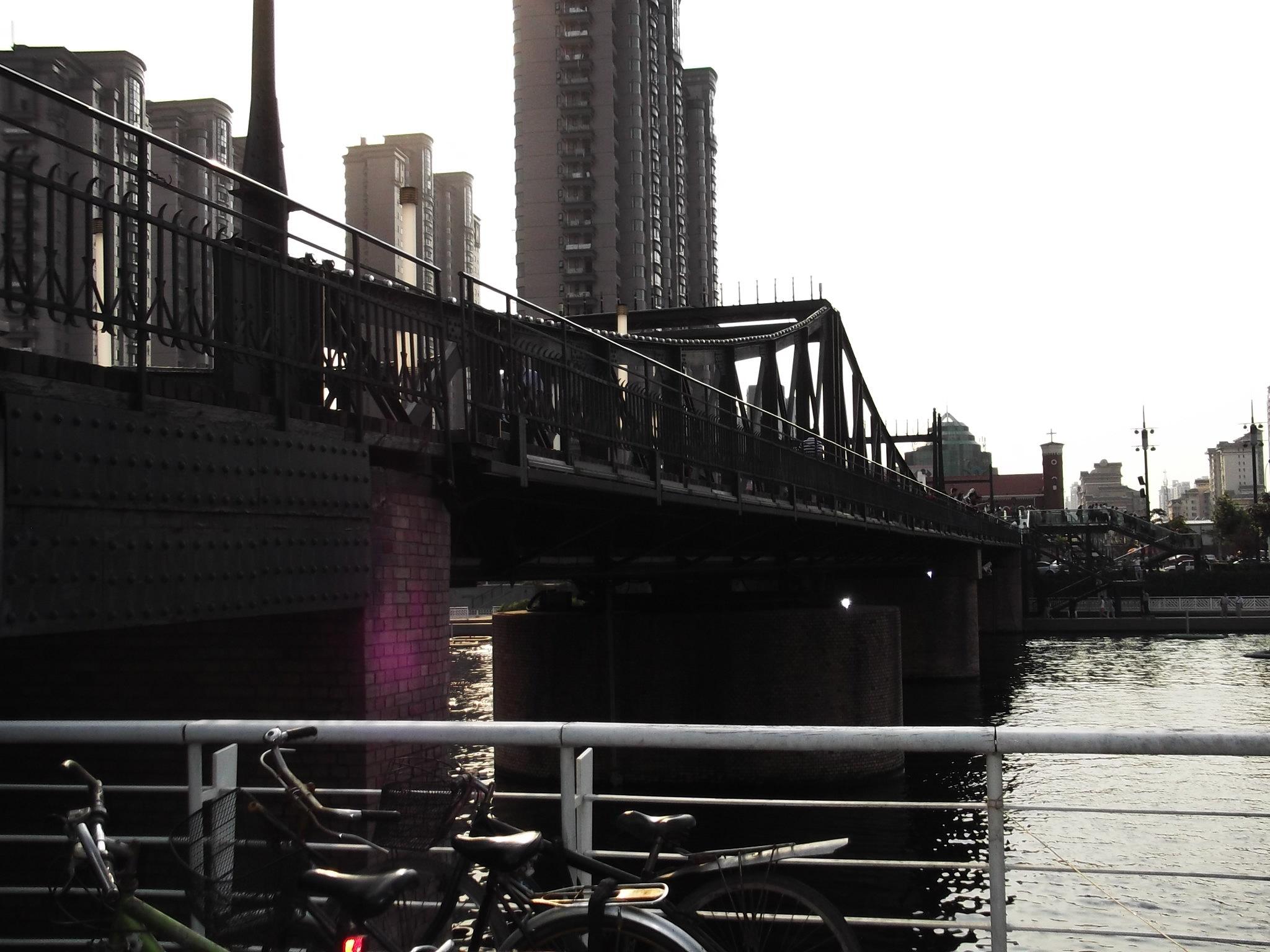天津解放橋又稱萬國橋,建于1927年,天津市的标志性建築之一,也是目前海河跨橋中僅剩的唯一一座可開啟的橋。解放橋連接着河北區的世紀鐘廣場與和平區的解放北路,位于天津火車站與解放北路之間的海河上,是一座全鋼結構可開啟的橋梁。 解放橋原名萬國橋,即國際橋之意,北連老龍頭火車站,南通紫竹林租界地。因當時的天津有英、法、俄、美、德、日、意、奧、比等9國租界,故得此名。而此橋位于法租界入口處,又是由法租界工部局主持建造的,所以當時天津民衆稱它為法國橋。抗日戰争勝利後,改名:中正橋。1949年,天津解放後此橋正式更名
