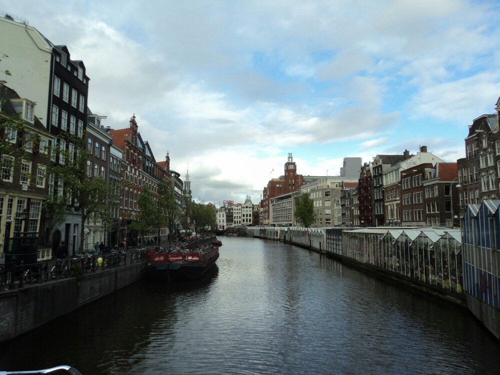 阿姆斯特丹原来这么通透、簇新、开阔。我以为它市内160多条运河与街巷、小桥缠绕,该像他人口中的威尼斯,城市呈下陷的沉重挤迫状,有些脏旧,游客如织。但它不是,新区有宽阔的河道和公寓楼,昂贵的公寓和廉租房混在一起,外观都一样漂亮;十多层的巨大客轮停在近处,小小的船屋上植满鲜花,人们在船上晒衣服,透过窗户,可以清楚看见房间里静谧的沙发和书架,餐桌上摆着的水果。而古老的运河区,老式山形墙房子依然鲜丽,和新的一样。光照很强,映着河面,反射在迅速经过的人们的单车上。