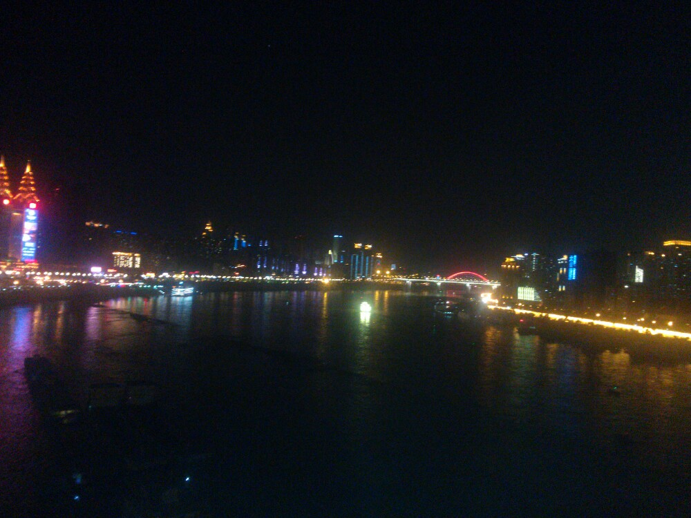 """长江客运索道,已经成为了游客在山城的必游项目。索道起于渝中区长安寺(新华路),横跨长江至南岸区的上新街(龙门浩)。乘上索道,滑向江对岸,一路可见近在咫尺的钢筋森林、长江以及江北南岸区的风光。 """"不览夜景,未到重庆"""",乘坐全程约千米的长江索道,是近距离俯看重庆夜景的绝佳体验。灯火辉煌的渝中半岛、璀璨夺目的滨江路、波光粼粼的长江水、流光溢彩的跨江大桥,交相辉映。如果你在蒙蒙细雨之夜,乘坐长江索道看夜景,还可欣赏到一幅水墨淡彩的《巴山夜雨图》,巴山雨态,水墨中的城市山林。 长江索道也成为"""