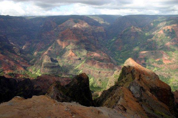 是云是雾?我们就说是云雾,弄的M一头雾水。 可爱岛的大峡谷长约16公里,深约900米。是WAIMEA河水长期以来侵蚀而成。在可爱岛的中间,有着世界上最潮湿的地方,每年的平均降雨量 有11米之多,那就是WAIMEA河的发源地。我们说水滴石穿,更何况可爱岛本身就是松软的火山岩!不过眼前的奇观仍然是500万年大自然不懈变迁的结 果。相对于亚利桑那州大漠之中大峡谷,眼前的WAIMEA多了一点绿色,多了一点云雾,也就多了一份柔和。如果说前者有着雄壮狂傲的男人之气的话,后者则是上帝从前者抽出的一根筋骨捏造之成。果真