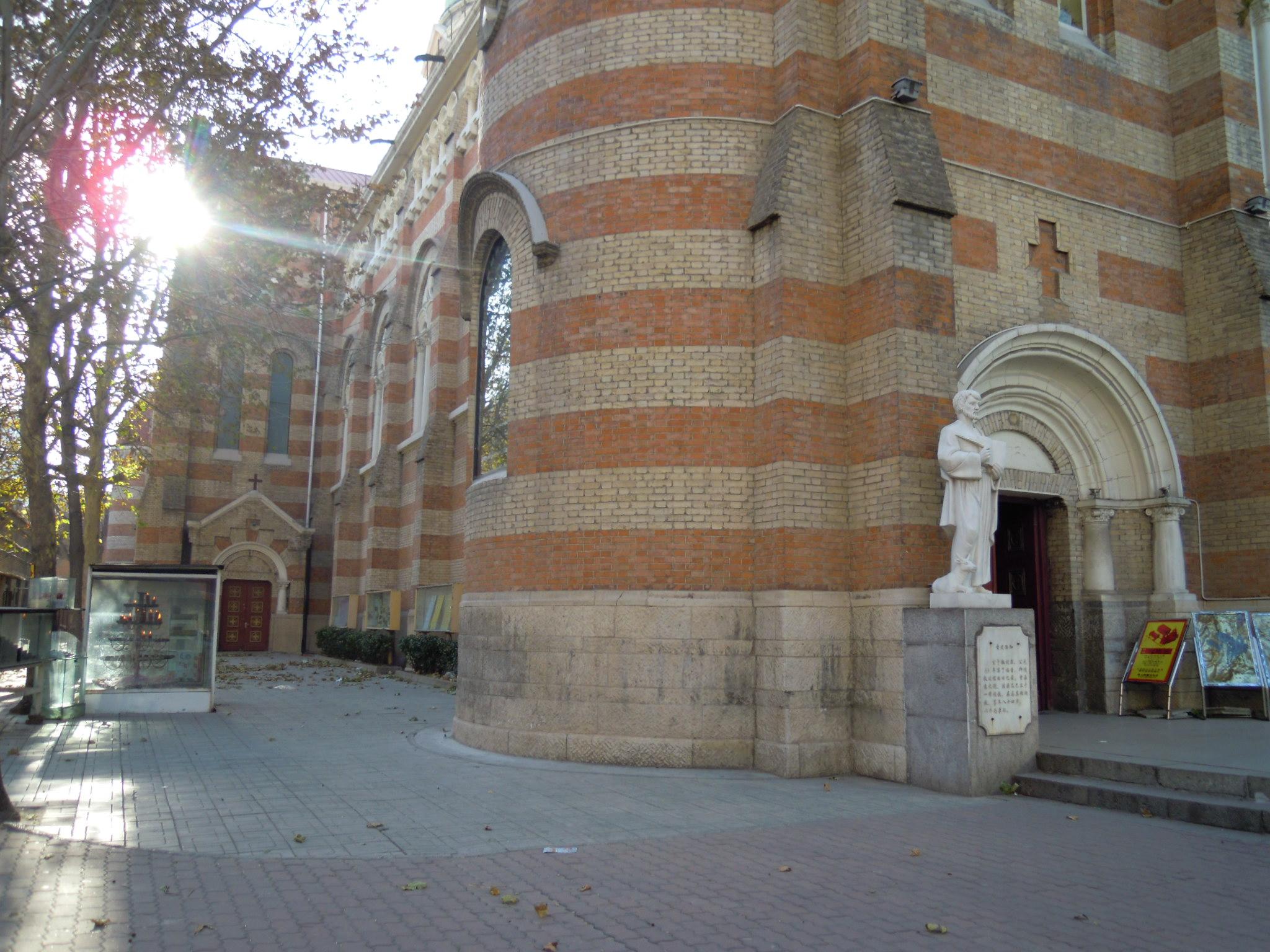 西开教堂位于繁华的滨江道商业街的最南端,始建于1917年,是天主教天津教区的主教堂。教堂建筑风格庄重大气,教堂内的雕塑也都繁复精美,另外弥撒和天主教节日的活动对外开放,可以参与其中,感受浓厚的宗教氛围。 外部参观 教堂外部用红黄相间花砖砌成,三座呈品字形排列、高耸入云的塔楼上浮盖着绿色铜片,经过岁月的冲刷,斑驳的绿色在阳光的照耀下反而闪烁出具有历史感的光彩,塔楼顶上各有一个青铜十字架。 内部建筑 走进教堂,映入眼帘的首先是湖蓝、白色、淡黄构成的内部主色调,给人一种清新的感觉,只在恰到好处的位置上雕刻着各种