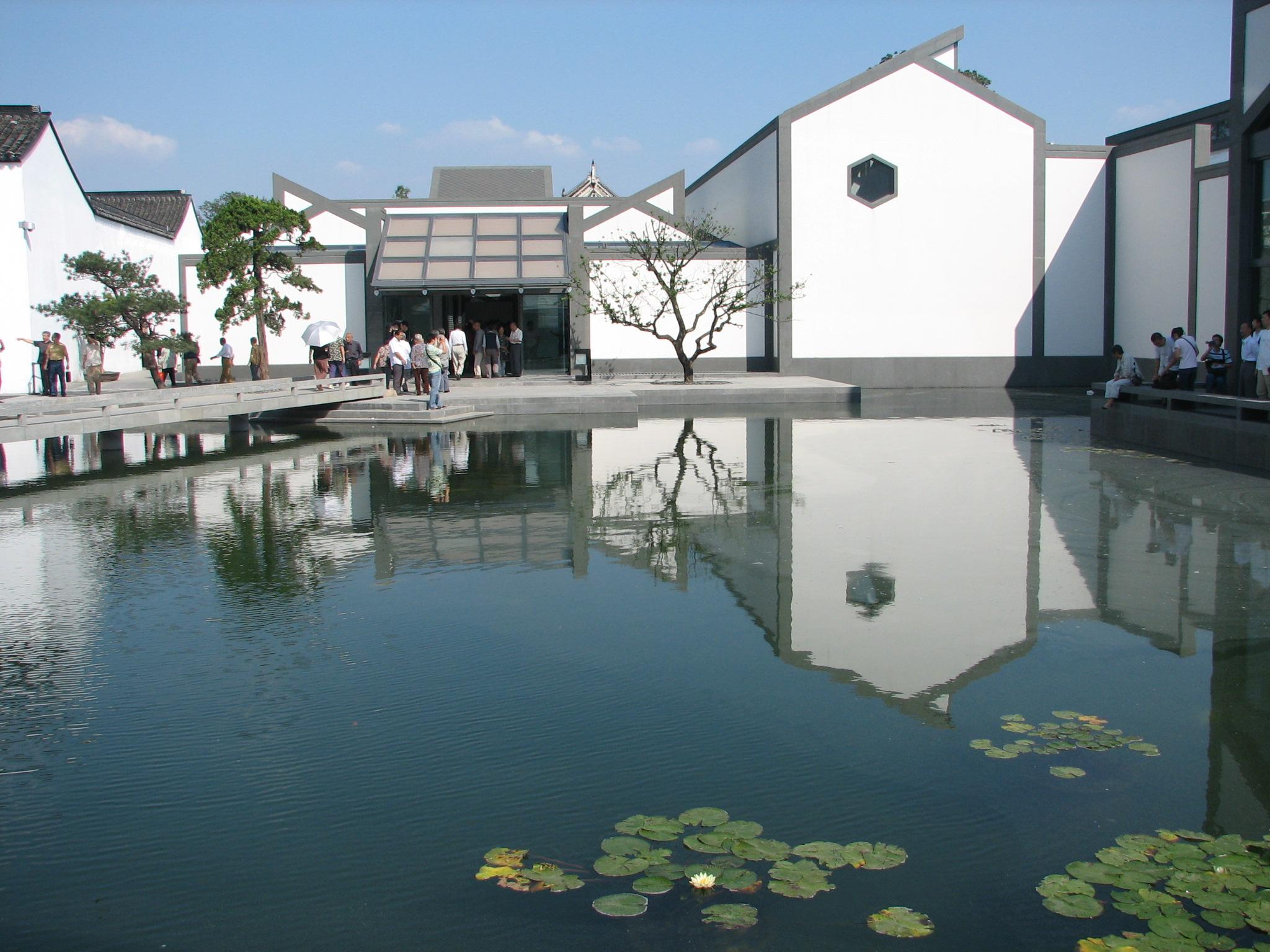 """苏州博物馆包括2006年起开放的新馆和太平天国忠王府古建筑(旧馆)两部分,整个博物馆就像一座小园林。在新馆内,可以看到从远古到近代的陶器、玉器、书画等文物;在忠王府内,还能看到秀丽典雅的""""苏式彩绘""""。 新馆大门是入口,忠王府大门是出口。进馆后可以好好欣赏一下这座新馆建筑,它由建筑大师贝聿铭设计,有着传统的苏州园林风格,高低错落,深灰色屋面与白墙相配,清新雅致。屋顶上金字塔形的玻璃天窗让博物馆内充满自然光线,在大门、天窗廊道、凉厅及各展厅都可以看到这个特点。馆中还有庭院、水池、石桥,"""
