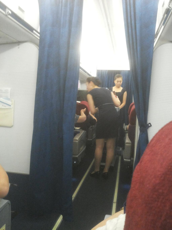 在飞机降落过程中,空姐系着安全带坐在空姐专用位置