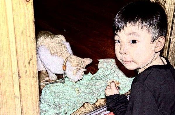 (偷拍小孩喂猫,小朋友被我的闪光灯吓了一小跳,整个小肩膀都剧烈的抖
