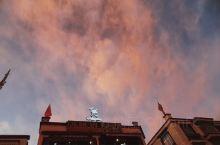 傍晚拉萨的街头,天空上晚霞很美,云朵是粉红的。