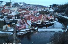在克鲁姆洛夫城堡上俯瞰冬日的小镇美景,蜿蜒曲折的伏尔塔瓦河逶迤远去,河上的小桥连接起两岸,屋顶的残雪