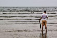 在烟台大学海水浴场看见一青年男子独自一个人在海边闲逛,海鸥在海滩上觅食。天气闷热,一种雨前的的感觉…