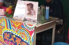 游客多的地方就充满了商机,眷村就开了一家小店买饮料特色彩绘商品,在一边坐着一个老爷爷。站在他身边的蜀