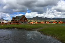 乌兰巴托的郊外度假别墅风景优美,蓝天白云,绿草茵茵,小河潺潺,蜿蜒在草原中,绿顶的欧式建筑矗立于草原