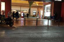 家乐福马拉加卖场,位于机场大道边。夜暮下停车场里,灯光灿亮,有微风夹细雨,幸有遮阳棚做伞挡,路面有些