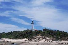 退潮时,在海滩礁石上正面远眺灯塔